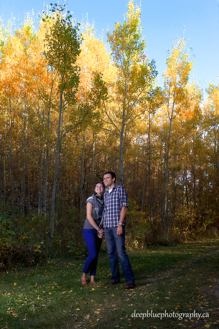Photo of Couple with Autumn Trees During Blackfoot Trails Engagement Pictures Session.