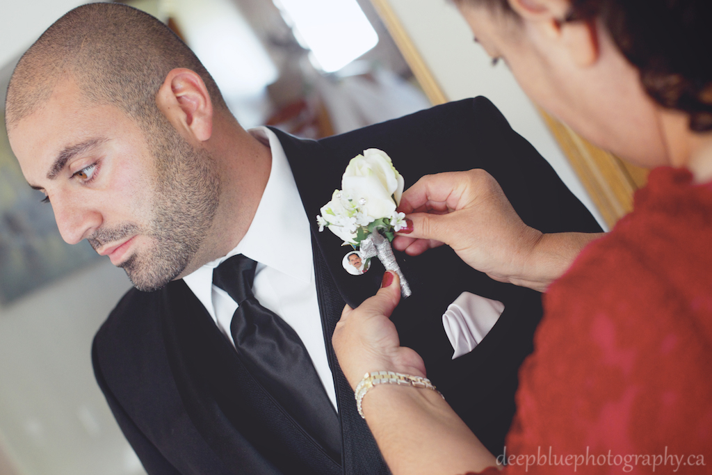 Photo of Groom with Mother Pinning Flower
