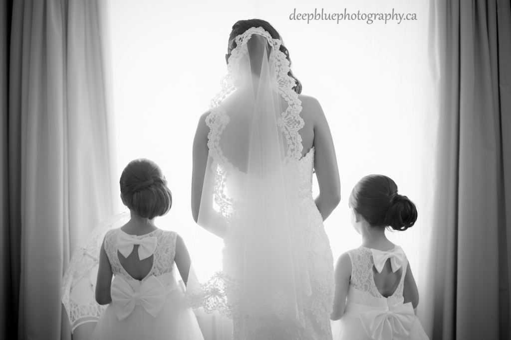 Photo of bride and flower girls looking out the window