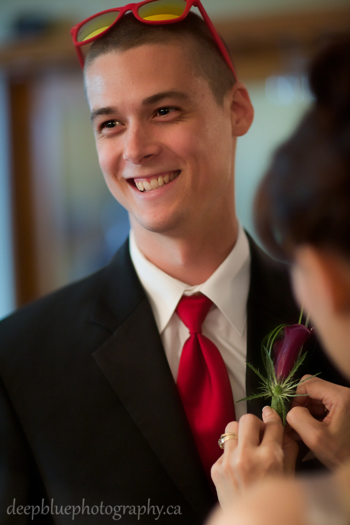 Groom has his flower pinned on by his mother