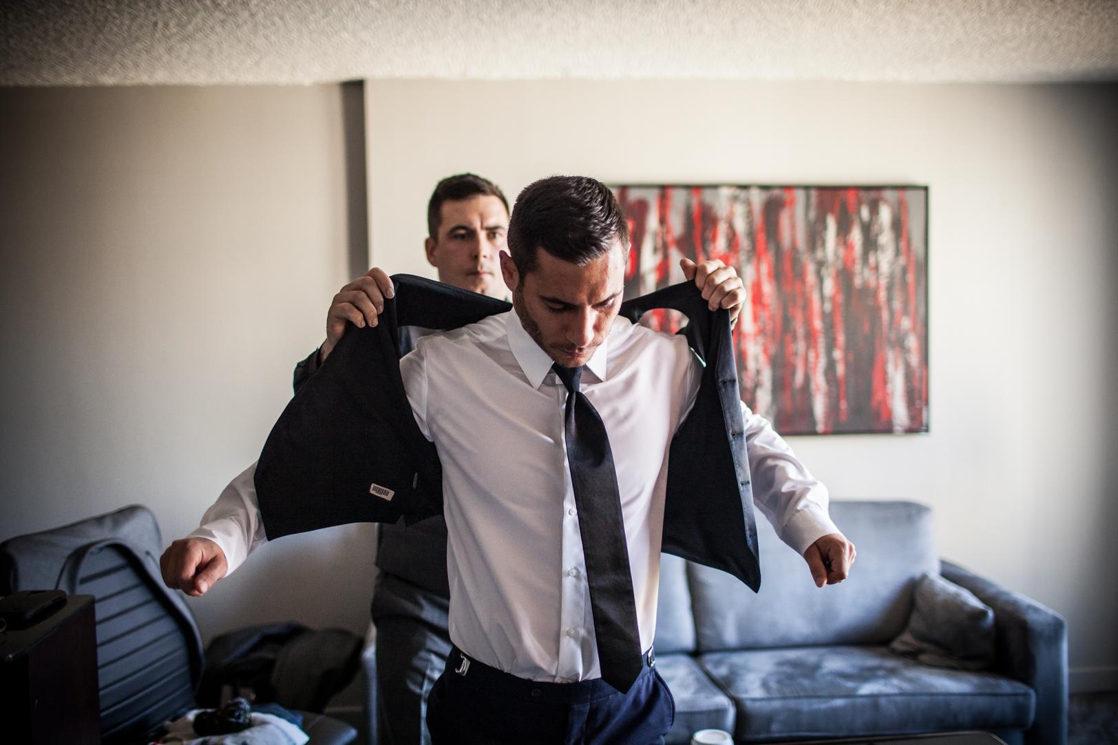 groom putting on jacket