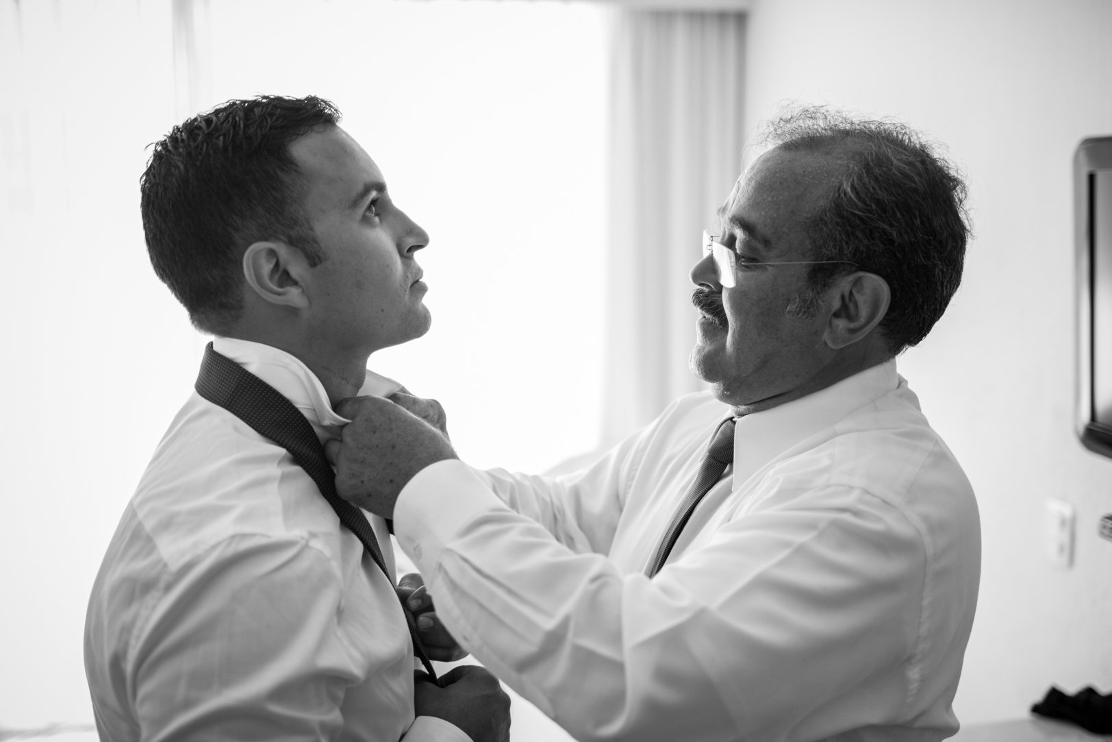 father helping groom with tie at Sunscape Dorado Pacifico Ixtapa destination wedding