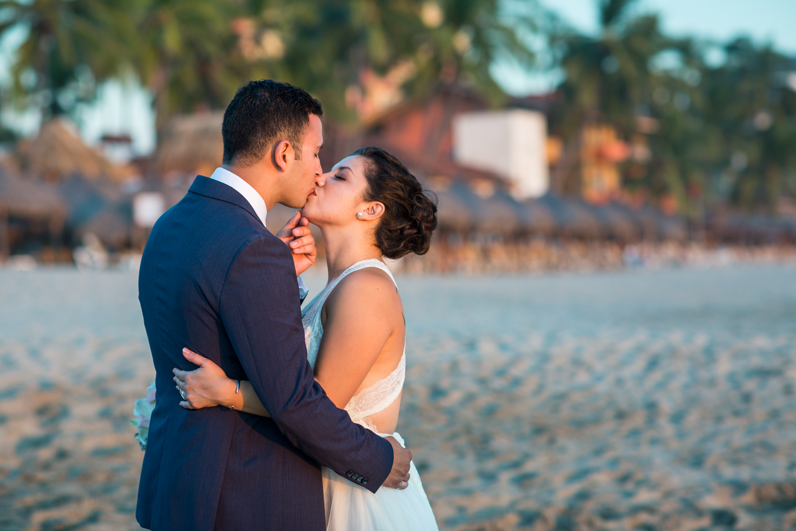 Bride and groom kissing on the beach at their Sunscape Dorado Pacifico Ixtapa destination wedding