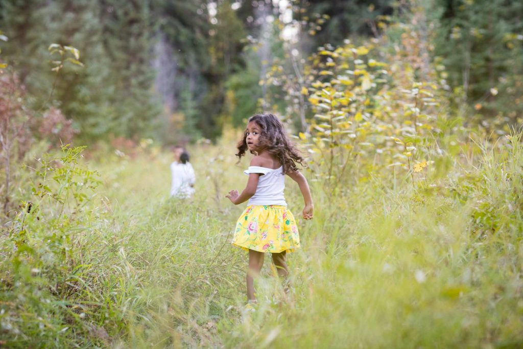 Kids playing in the grass during family photos in Edmonton