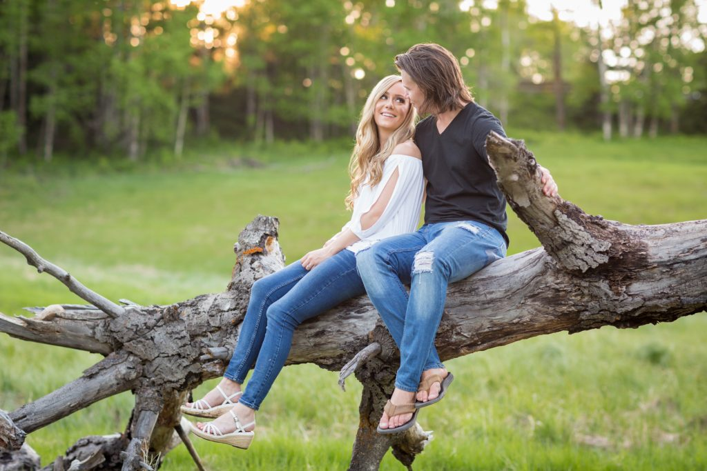 Couple sitting on a large fallen tree