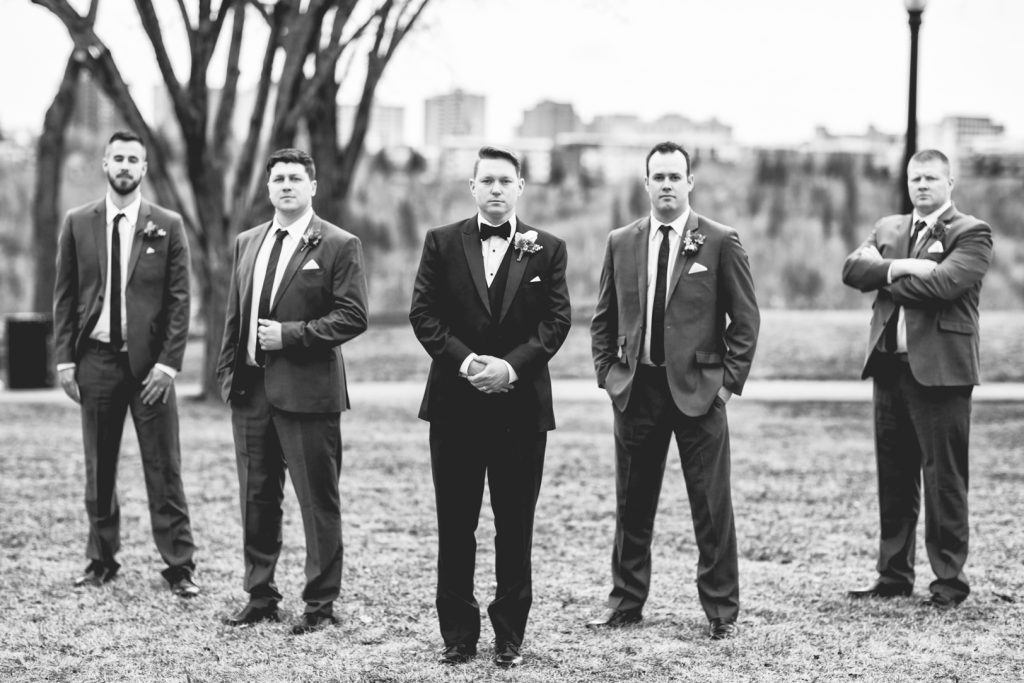 Photo of grooms men during outdoor wedding portraits