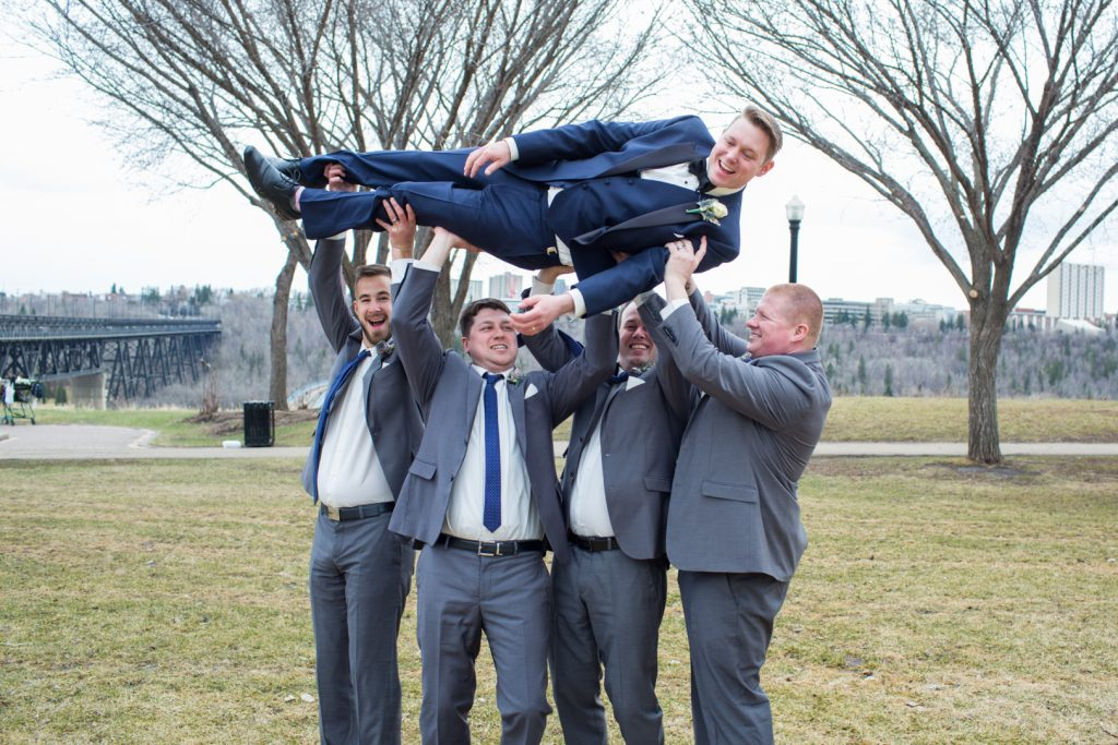 Groomsmen holding up the groom