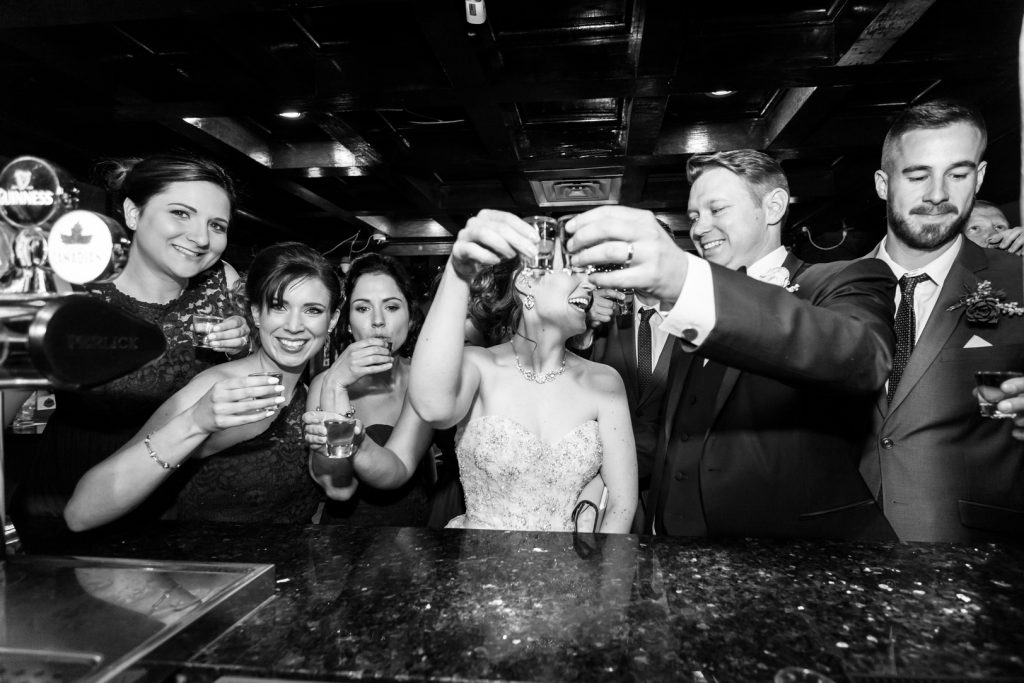 Wedding party taking photos in local bar