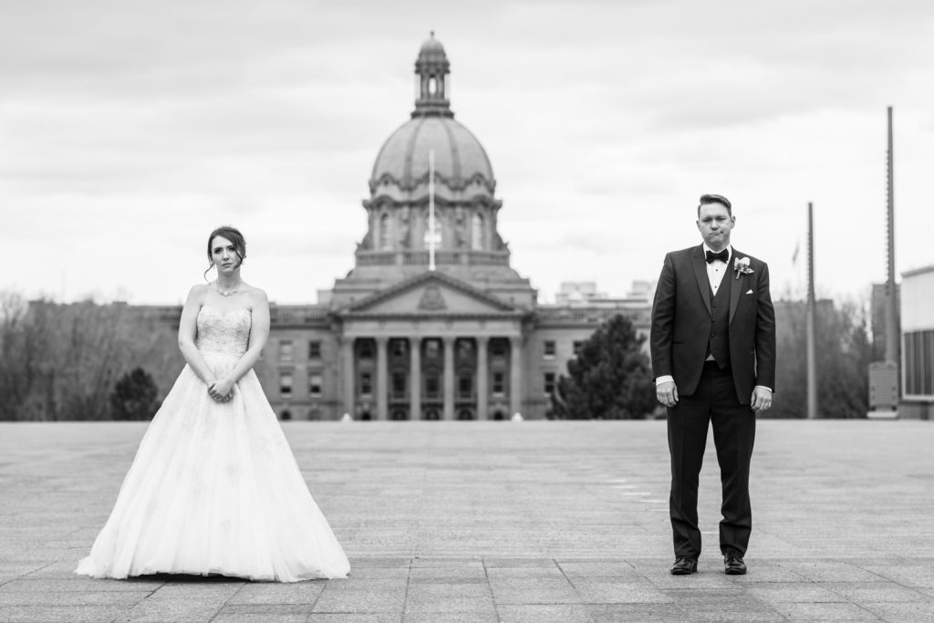 Couple stands for an awkward wedding photo in front of Alberta Legislature