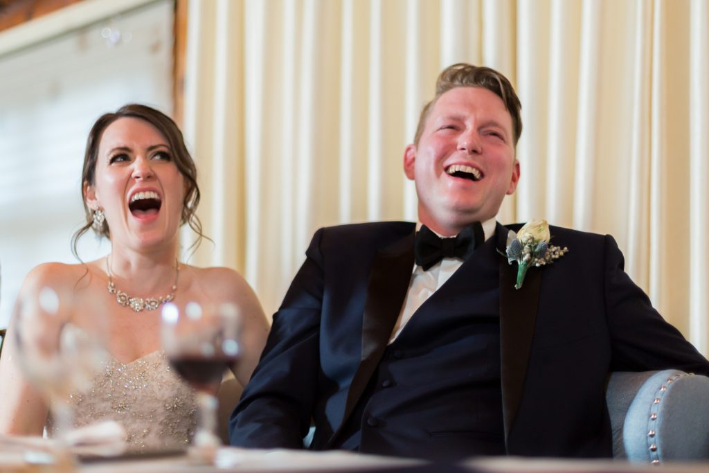 Bride and groom laughing during wedding speeches