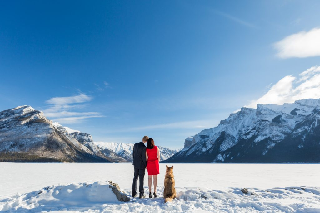 Couple with Husky at Lake Minnewanka - Mountain Engagement Photography by Deep Blue Photography