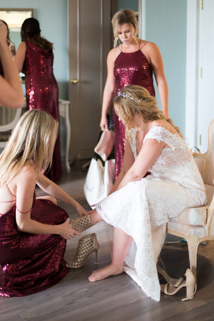 bridesmaids helping the bride put on her gold wedding heels