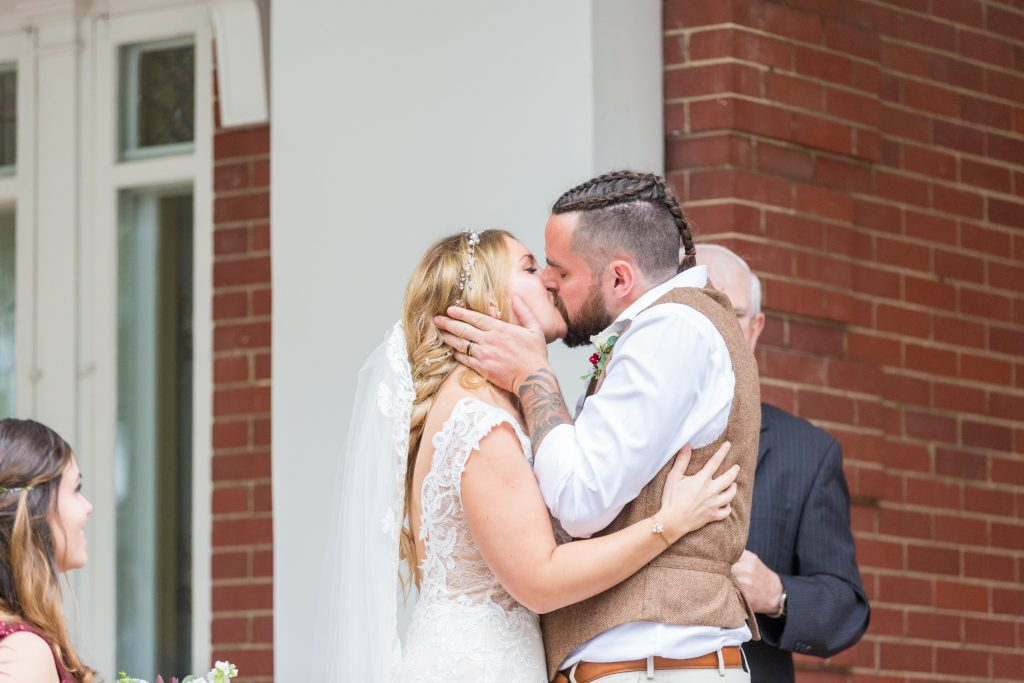 bride and groom first kiss outdoor wedding magrath mansion