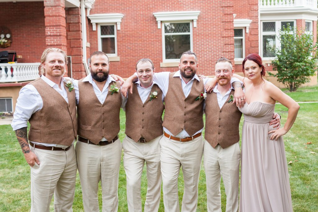 Groomsmen in brown vests outdoor wedding