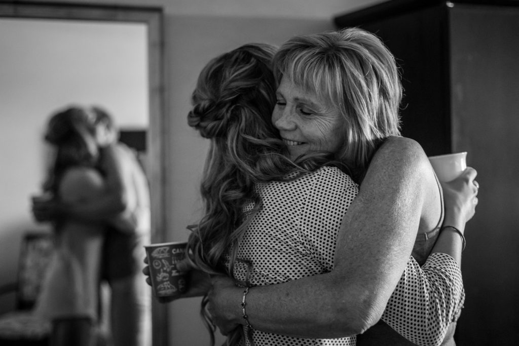 bride hugging her mother in law while getting ready at the hotel before the wedding