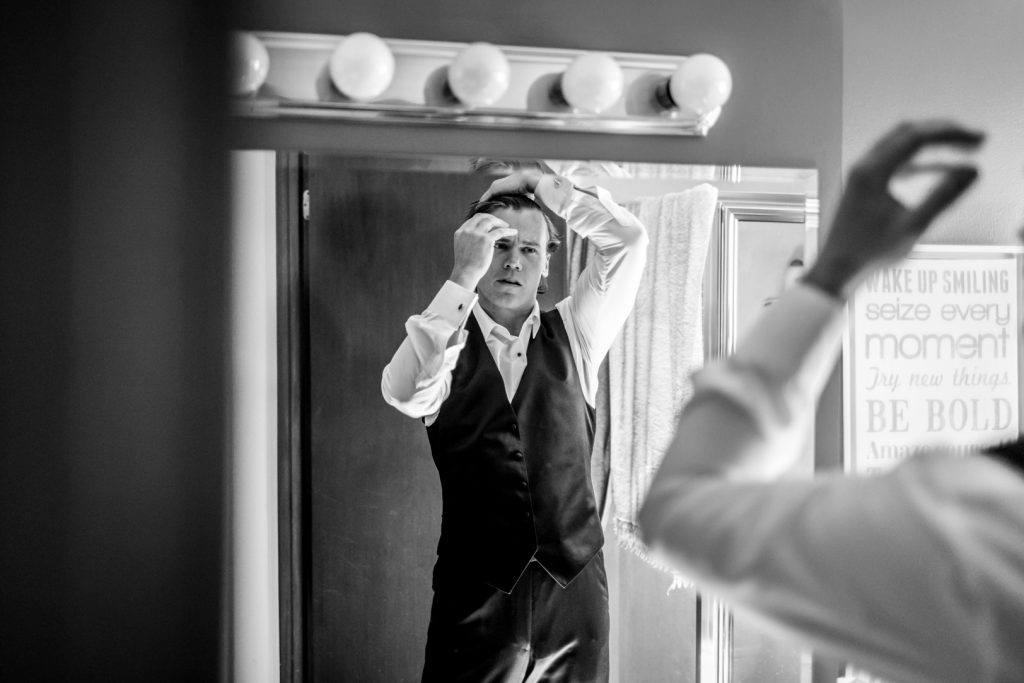 groom doing his hair while getting ready for the wedding ceremony