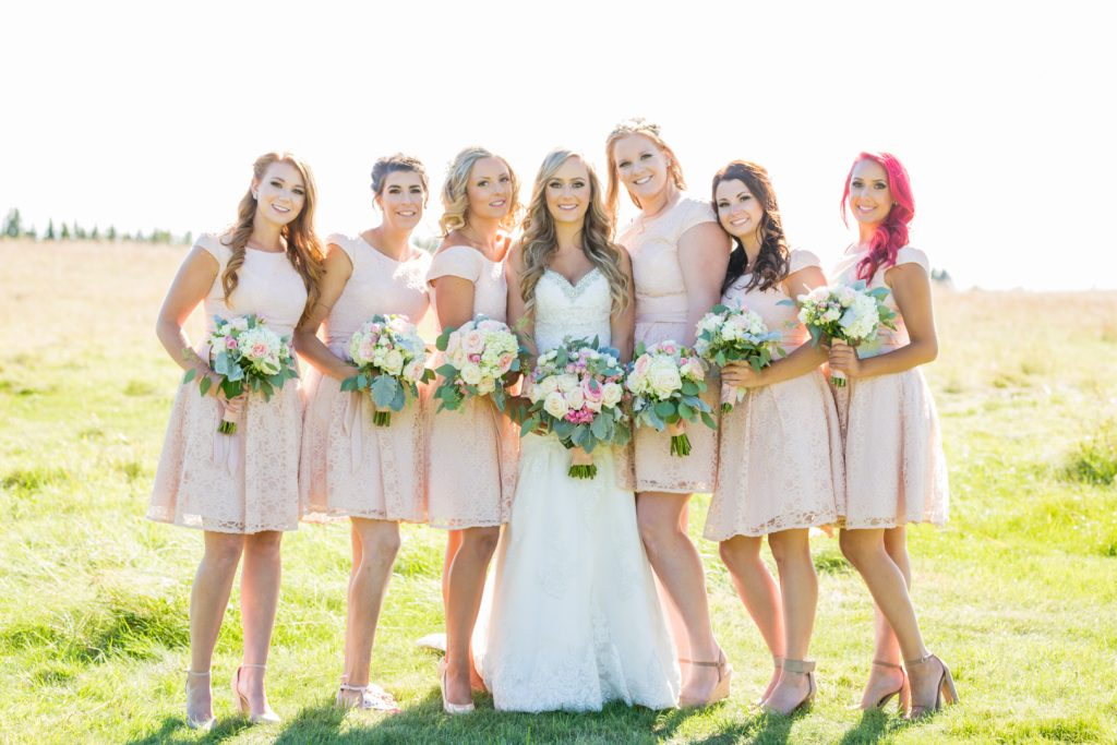 Formal wedding portrait of bride and bridesmaids wearing blush dresses