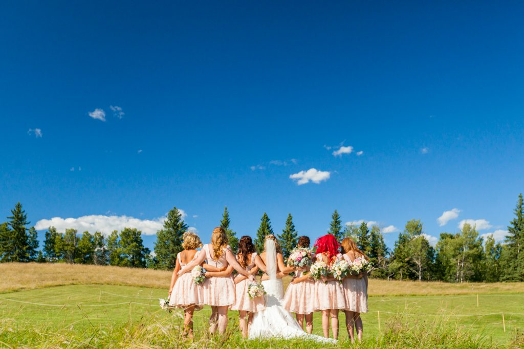 Bride and bridesmaids standing in a wheat field