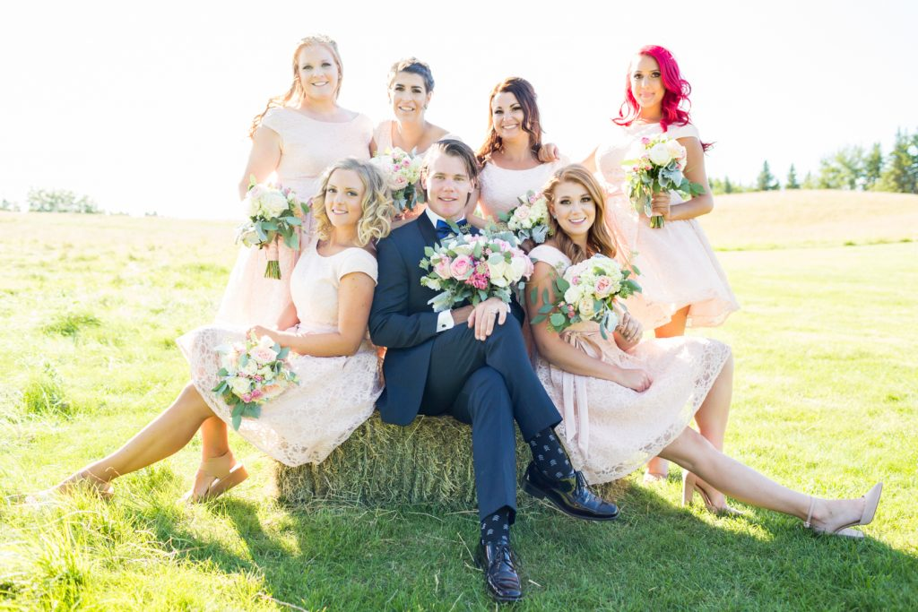 groom sitting with the bridesmaids