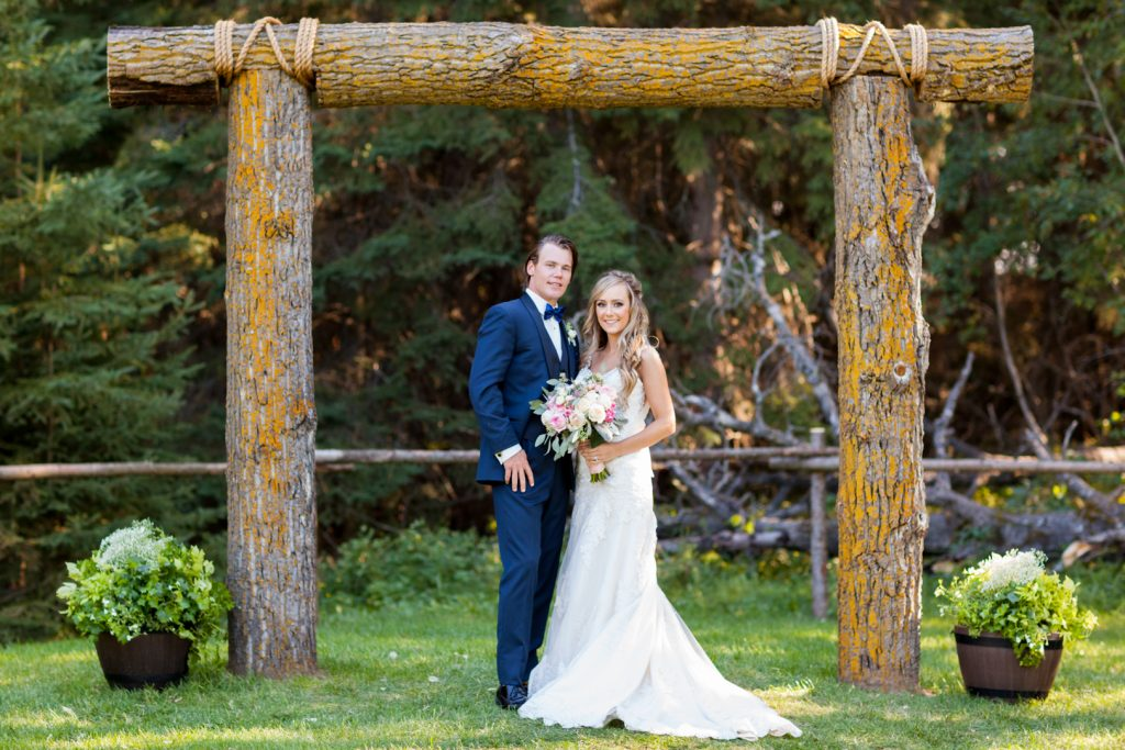 Wedding portrait of bride and groom standing under a large log archway