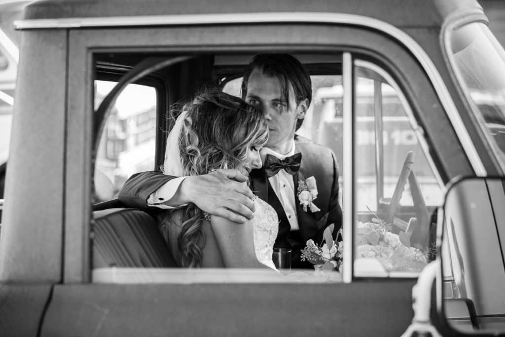 couple snuggled up on the front seat of an old pick up truck