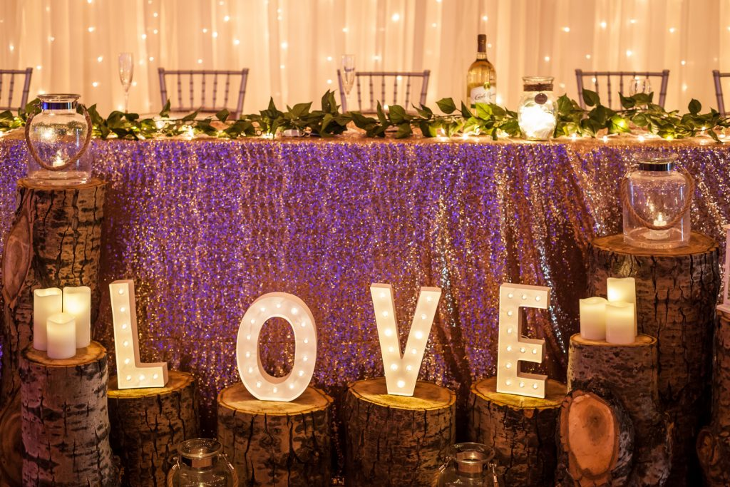 Marquee letters spelling love at the head table at wedding reception