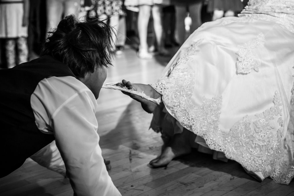 Groom pulling the garter off the bride's leg