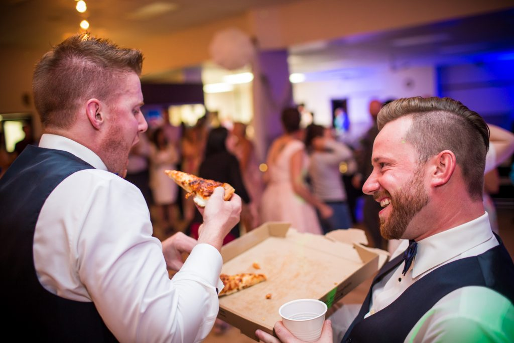 Guests eating pizza for midnight lunch at wedding