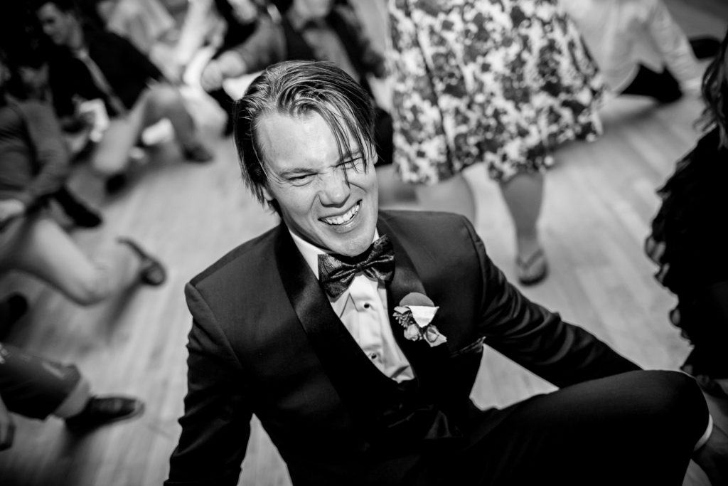 Photo of groom dancing during reception