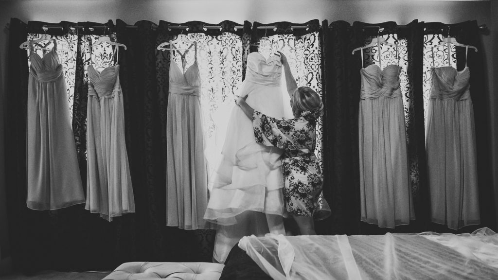 Bride reaching for her wedding gown as she gets ready in the morning