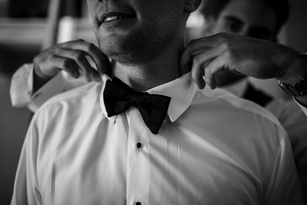 Groom putting on his bowtie