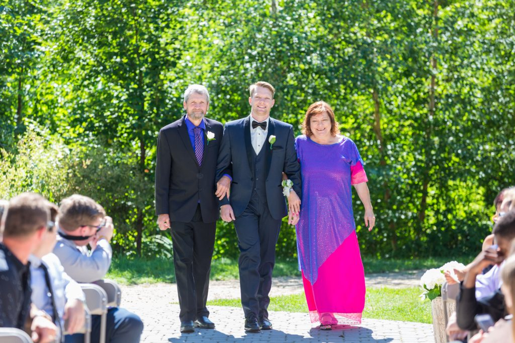 Groom being walking down the aisle by his parents