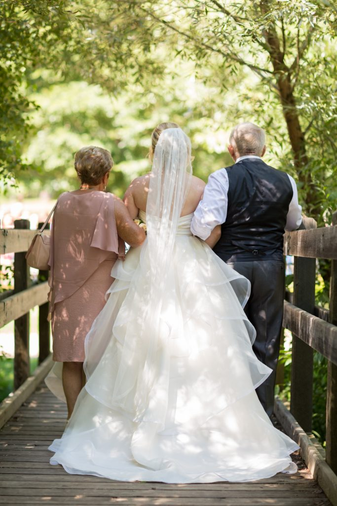 Bride standing with her parents waiting to walk down the aisle