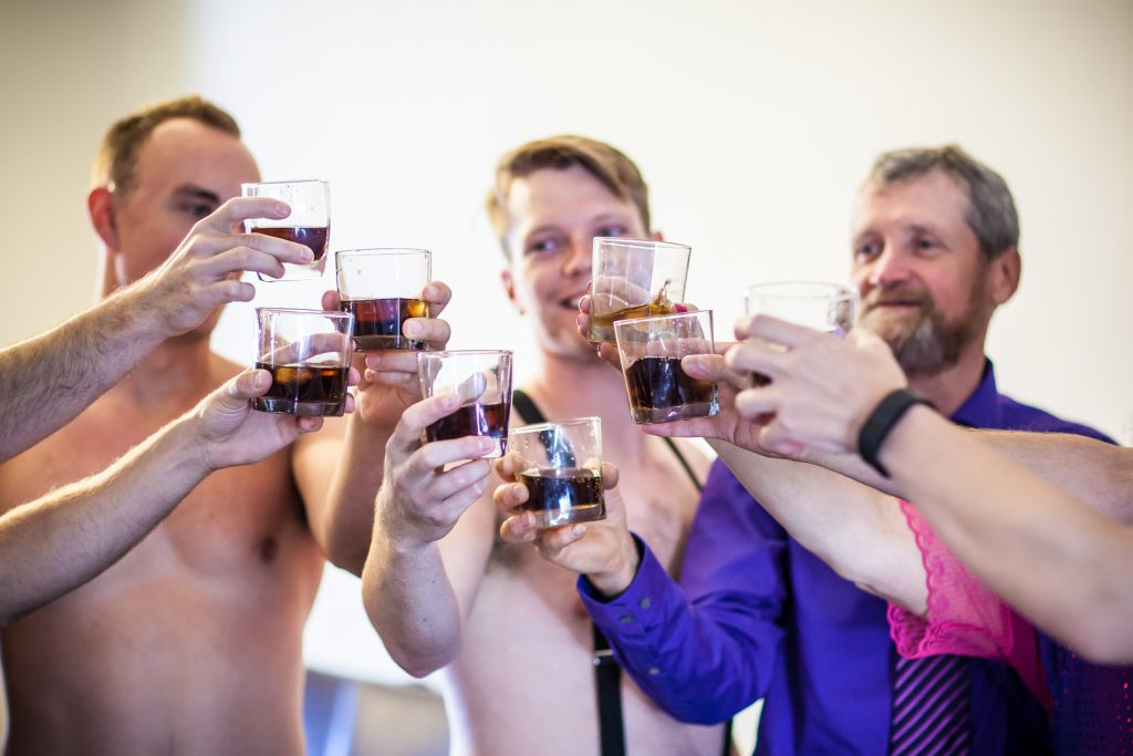 Groom and groomsmen having a drink while getting ready