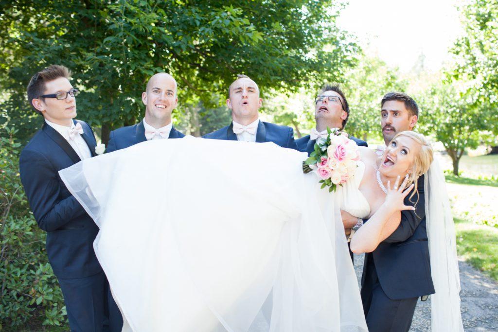 Groomsmen holding up the bride during wedding photos at botanic gardens