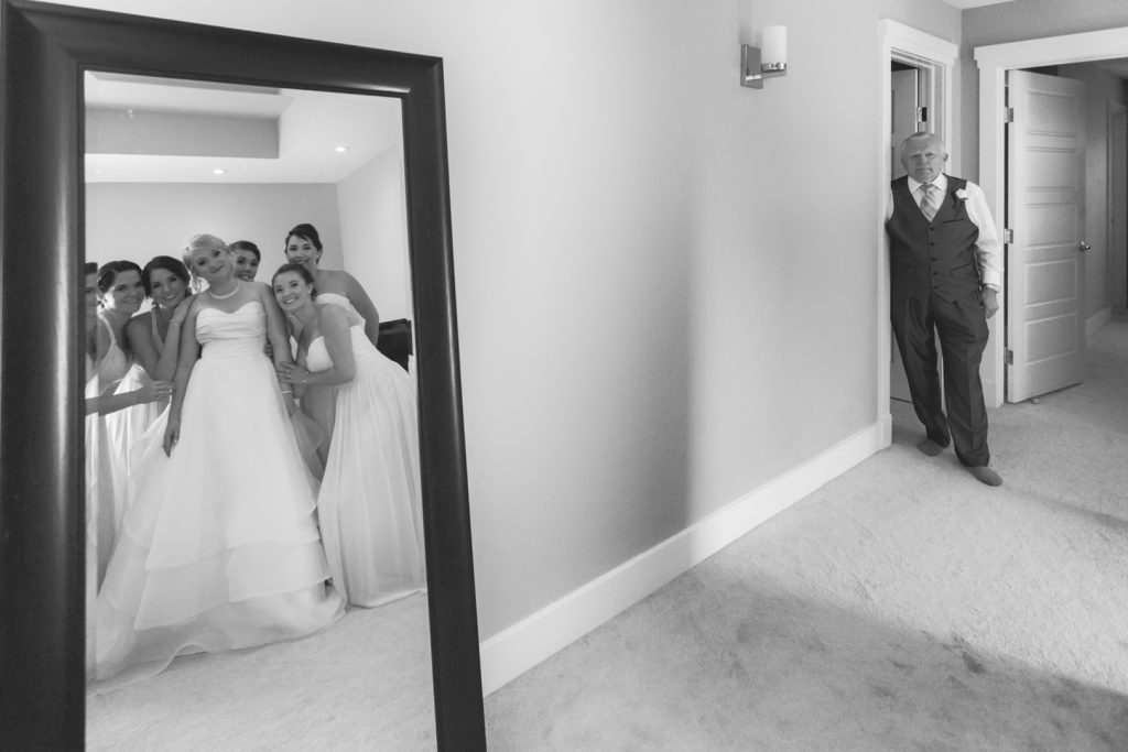 Reflection photo of bride with her bridesmaids with her dad off to the side
