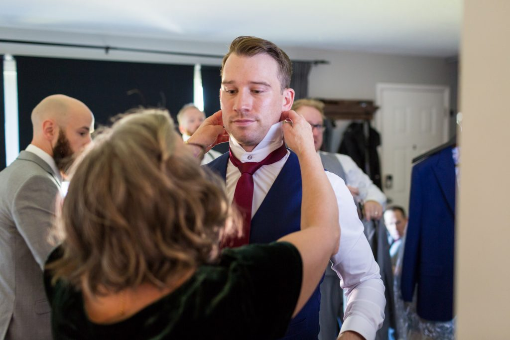 Mother of the groom helps her son put on his tie before Shaw Conference Centre wedding