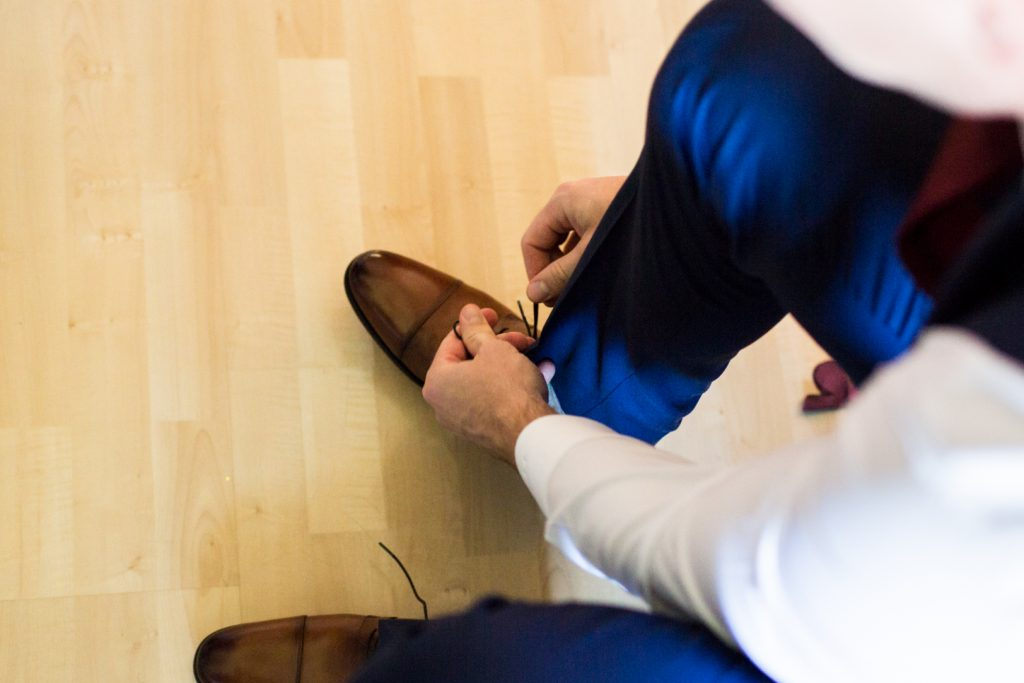 Groom puts on his shoes before Shaw Conference Centre wedding ceremony