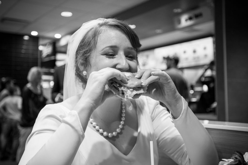 Bride eating burger at MacDonalds during wedding portraits following St Thomas More wedding ceremony
