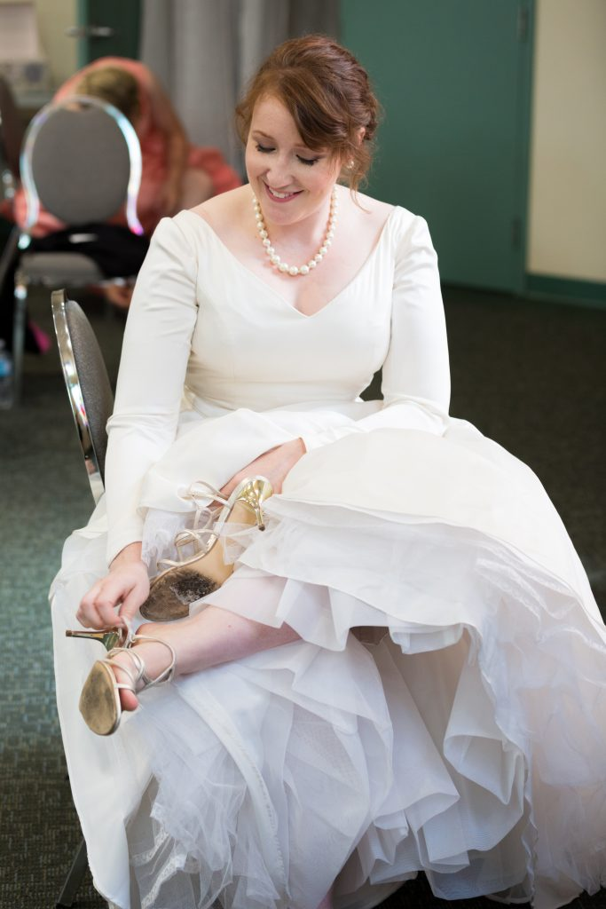 Bride putting on her shoes and getting ready for her wedding at St Thomas More Church