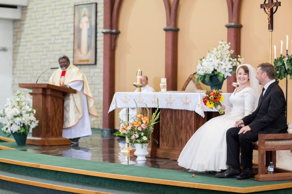 St Thomas More Church wedding ceremony with the bride and groom sitting on the stage