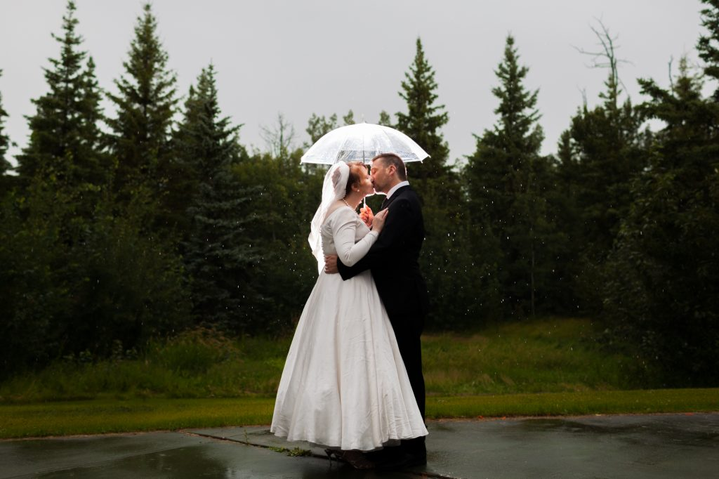 Bride and Groom holding each other close under an umbrella during rainy wedding portraits