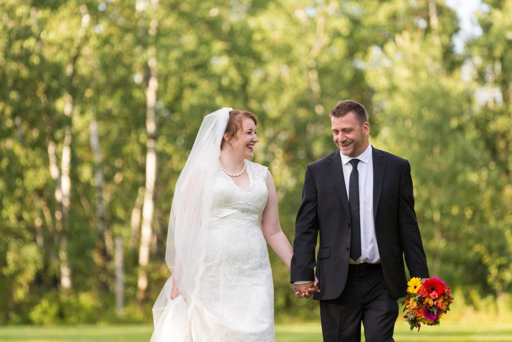 Bride and groom walking and holding hands during their portraits after their St Thomas More Church wedding