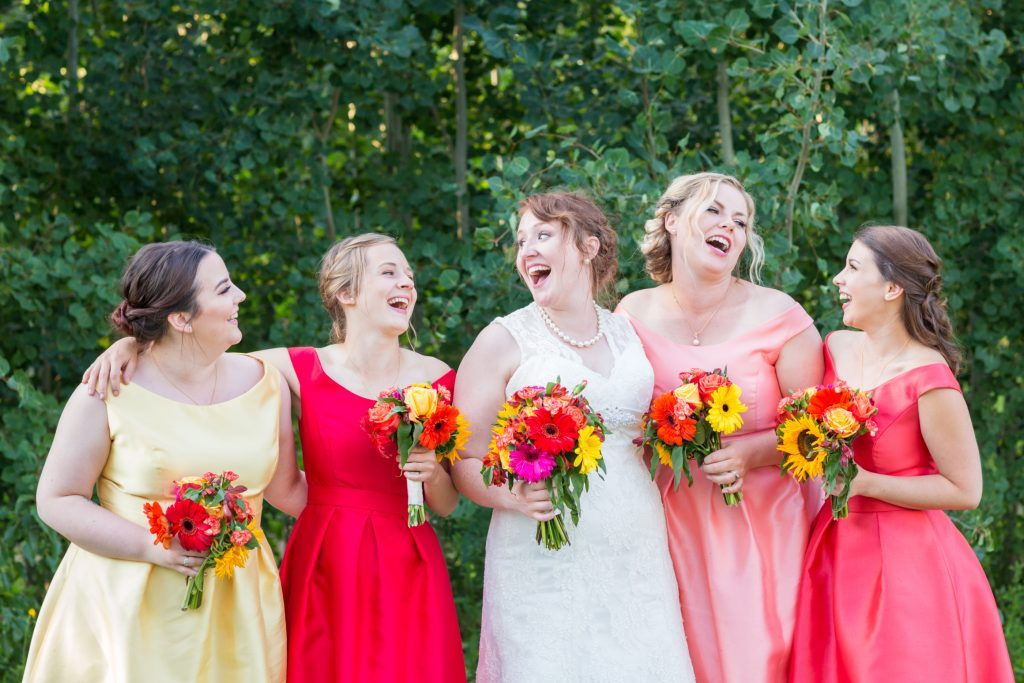 Rainbow coloured bridesmaids dresses for a summer wedding at St Thomas More Church