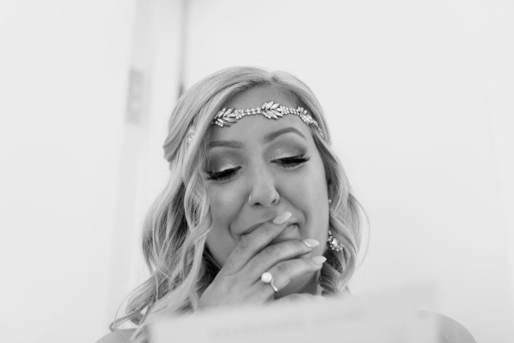 Emotional bride reading a love letter from the groom before outdoor summer wedding at Snow Valley