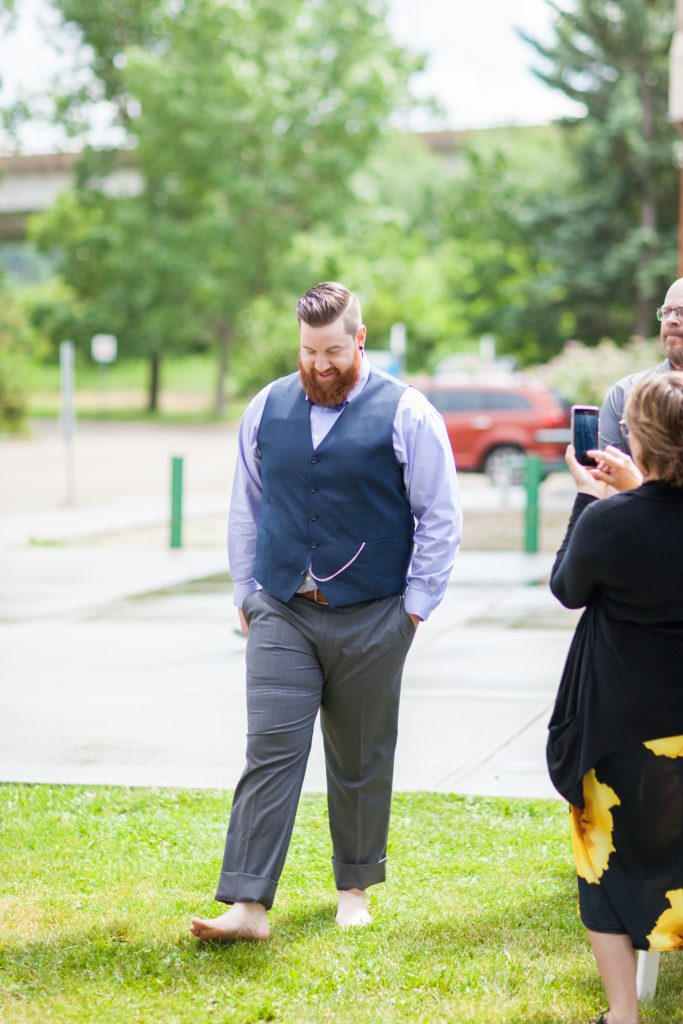 The groom takes his shoes off before to walk barefoot during summer wedding at Snow Valley