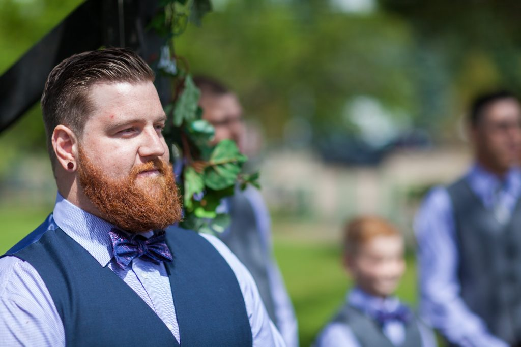 The groom waits to see his bride for the first time during their Snow Valley wedding in the summer