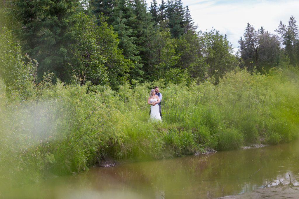Bride and groom beside the creek that runs through Snow Valley Park in Edmonton
