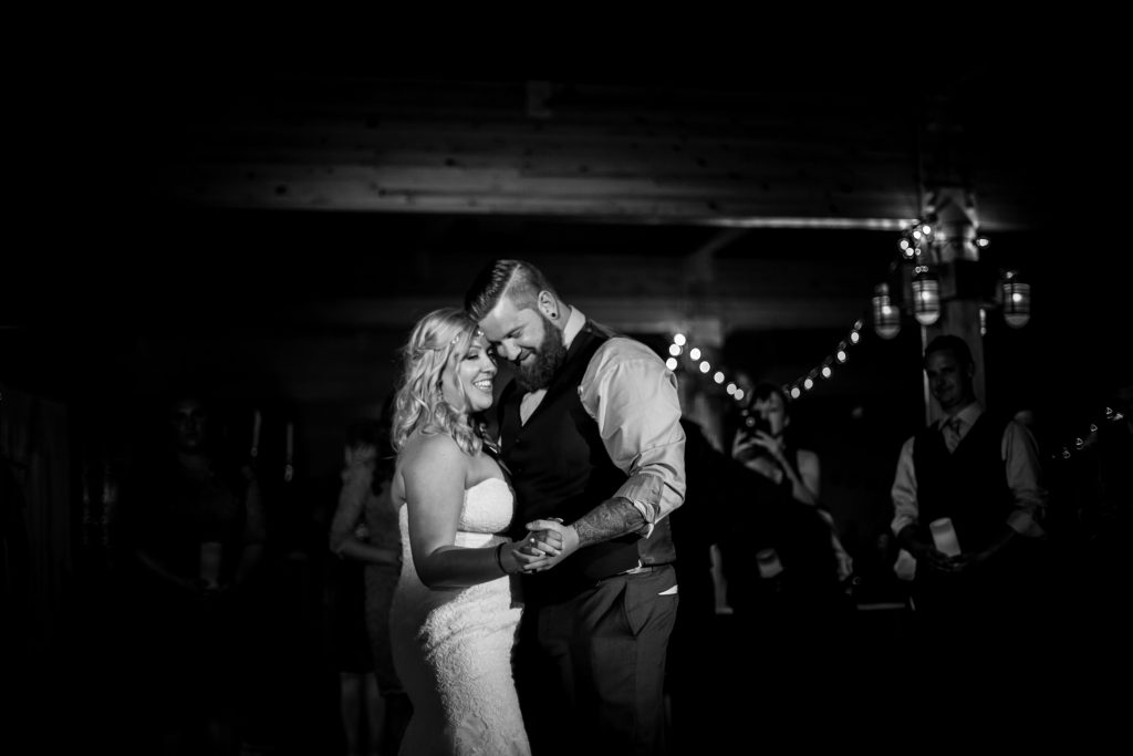 Bride and groom share their first dance during their summer wedding celebration at Snow Valley