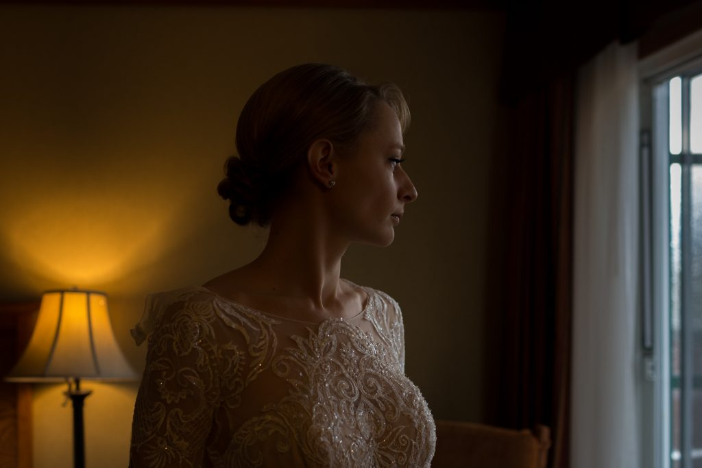 Portrait of the bride looking out the window before her winter wedding at Pyramid Lake